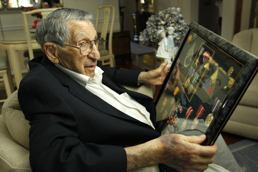 Lester Tenney examines his memorabilia from World War II