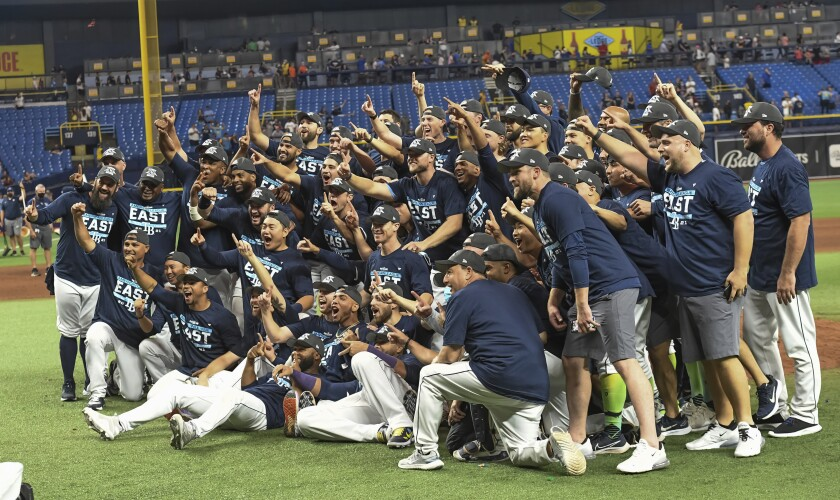 Tampa Bay Rays players and coaches celebrate after beating the Miami Marlins 7-3 to clinch the American League East during a baseball game Saturday, Sept. 25, 2021, in St. Petersburg, Fla. (AP Photo/Steve Nesius)