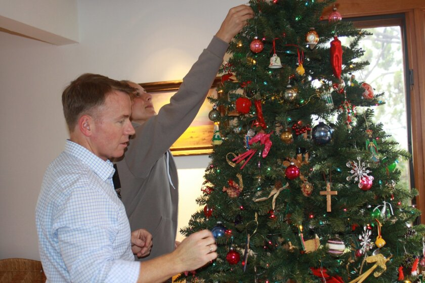 Paul Silvera and Aubrey Lair decorate the riley's tree with the family's own ornaments.