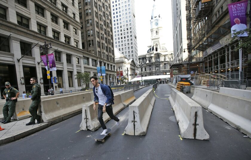 A man on a skateboard rides through a security checkpoint on Broad Street with City Hall in the background in Philadelphia on Friday, Sept. 25, 2015, before Pope Francis' upcoming visit. (AP Photo/Alex Brandon)