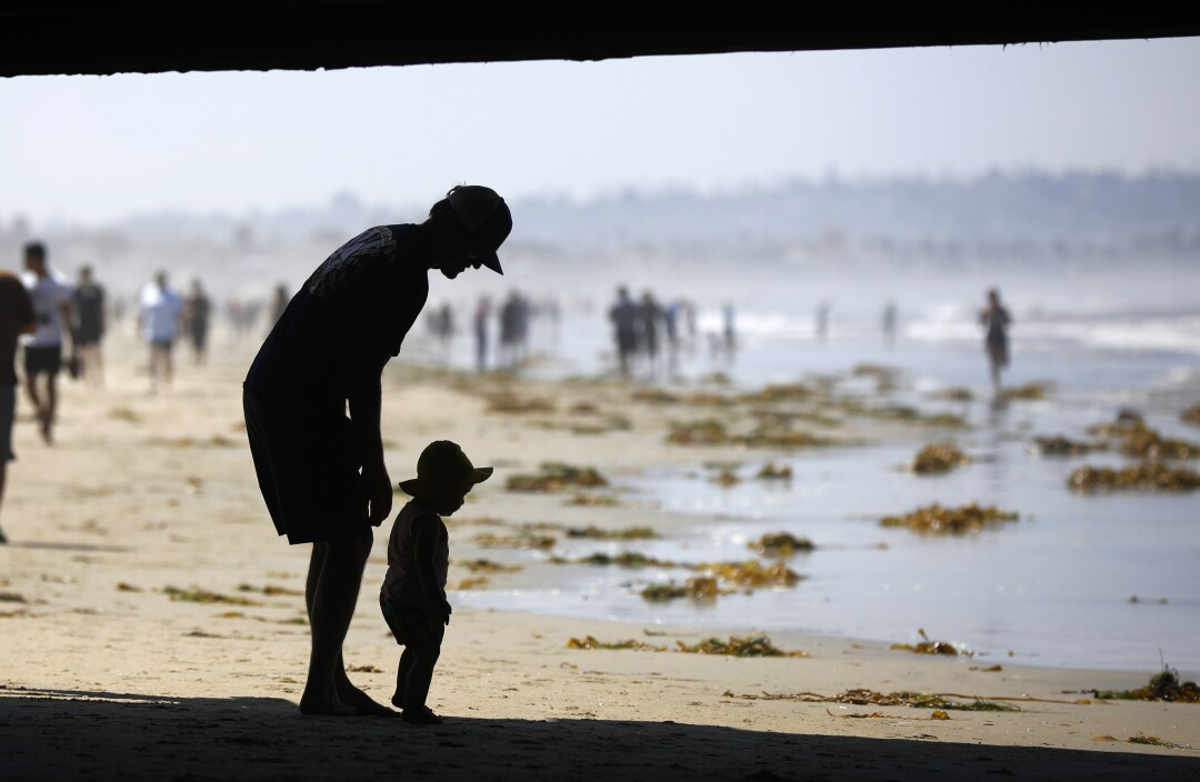 Thomas Kelley waks with his daughter Khailani under the Crystal Pier in Pacific Beach after local beaches reopened to activities such as walking, running, and surfing on April 27, 2020. Beaches have been closed for several weeks due to the coronavirus.