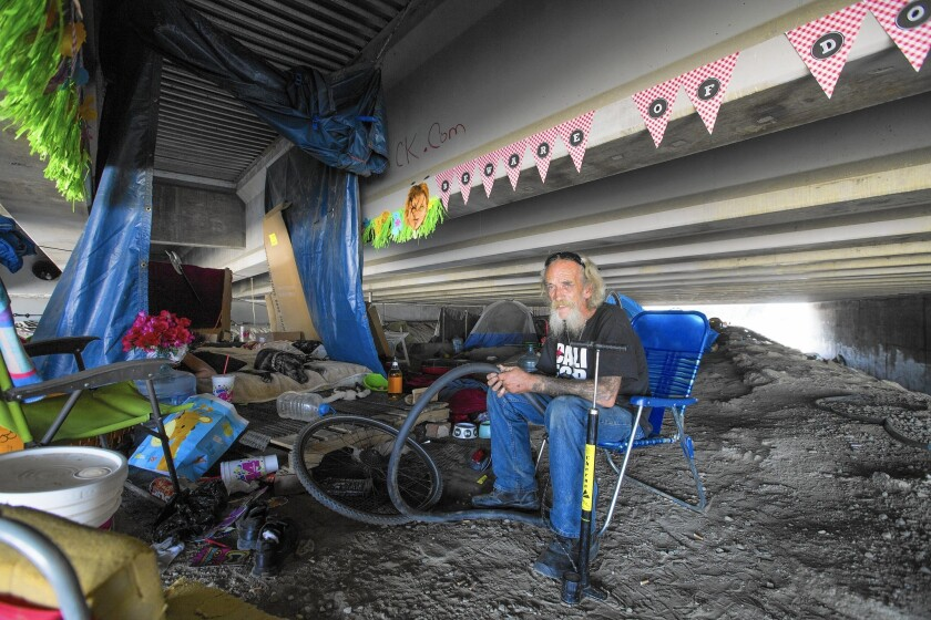 """Bill """"Tattoo"""" LeBlanc, 74, fixes a bicycle inner tube near his encampment in the Santa Ana River under the 5 Freeway in Orange. Hundreds of riverbed dwellers are at risk of drowning in heavy winter rains."""