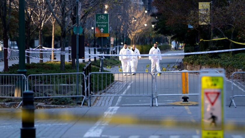 Emergency officials walk near evidence markers on the west side bike path in lower Manhattan, New Yo