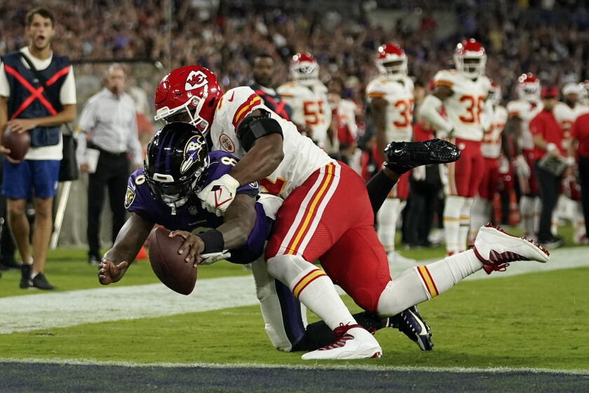 Baltimore Ravens quarterback Lamar Jackson dives for a touchdown against Kansas City Chiefs defensive end Michael Danna in the second half of an NFL football game, Sunday, Sept. 19, 2021, in Baltimore. (AP Photo/Julio Cortez)