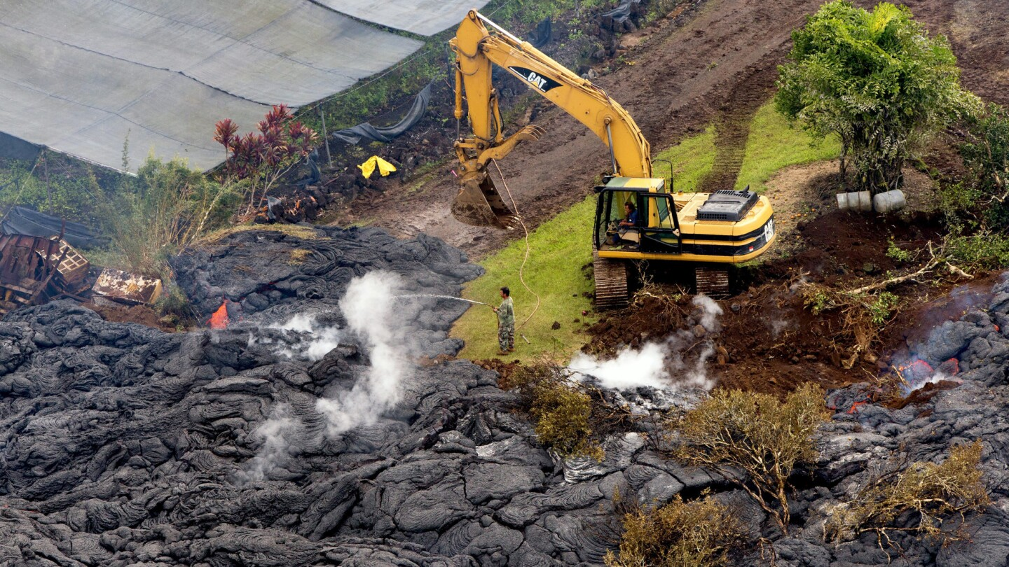 A homeowner tries to slow the flow of lava that threatens the village of Pahoa, Hawaii.