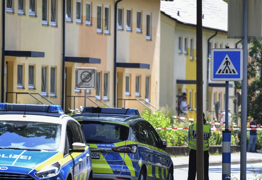 Police officers stand in front of a house in Espelkamp, Germany, Thursday, June 17, 2021. According to the Bielefeld police, two people have been shot in Espelkamp. The victims were a man and a woman and the circumstances are unclear but authorities said there appeared to be no danger to the general public. (Lino Mirgeler/dpa via AP)