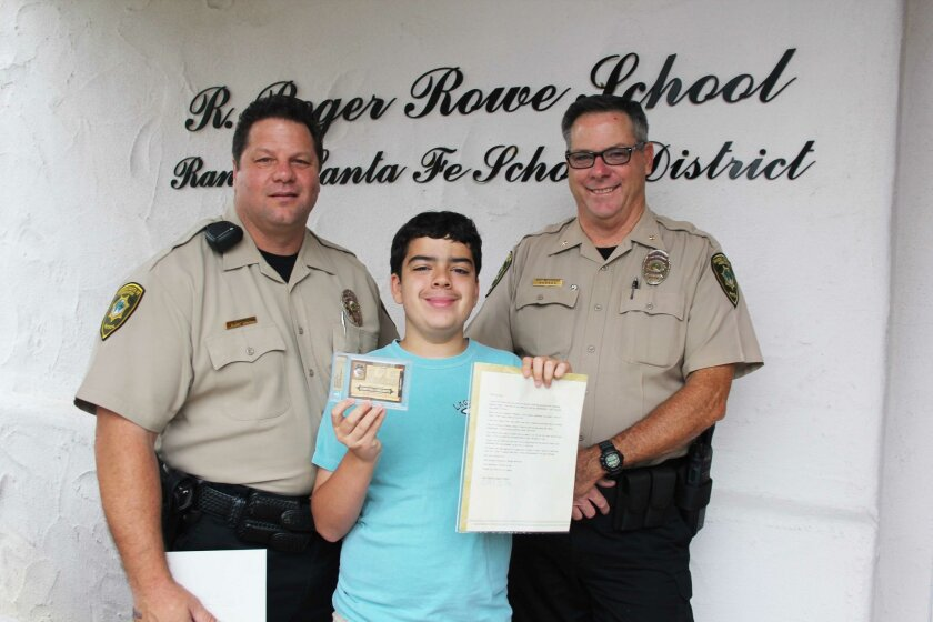 Rancho Santa Fe Patrol Officer Rick Petoscia with his friend, Carson Wehlage, and RSF Patrol Chief Matt Wellhouser. Officer Rick gave Carson a one-of-a-kind Lou Gehrig baseball card. Photo by Karen Billing