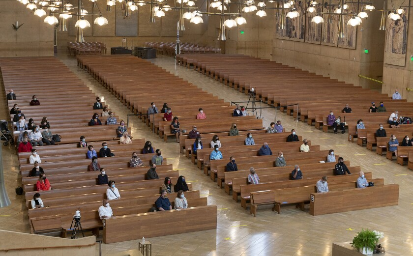 "FILE - In this Sunday, June 7, 2020, file photo, a hundred faithful sit while minding social distancing, listening to Los Angeles Archbishop Jose H. Gomez celebrate Mass at Cathedral of Our Lady of the Angels, the first Mass held in English at the site since the re-opening of churches, in downtown Los Angeles. Attendance at the Mass is limited to 100 people. California Gov. Gavin Newsom on Monday, July 13, 2020, extended the closure of bars and indoor dining statewide and ordered gyms, churches and hair salons closed in most places as coronavirus cases keep rising in the nation's most populated state. Newsom has compared his strategy of opening and closing businesses as a ""dimmer switch,"" highlighting the flexibility needed as public health officials monitor the virus's progress. (AP Photo/Damian Dovarganes, File)"