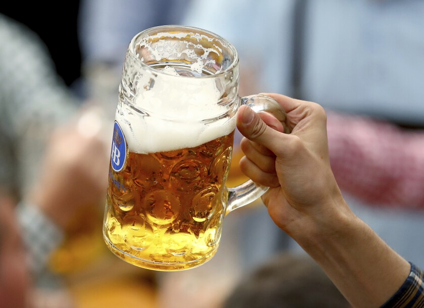 FILE - In this Sept.21, 2019 file photo a guest holds glasses of beer during the opening of the 186th 'Oktoberfest' beer festival in Munich, Germany. German beer sales in this year's first half were 2.7% lower than a year earlier. They were dragged lower by closures of bars and restaurants that stretched through winter and into spring. (AP Photo/Matthias Schrader, file)