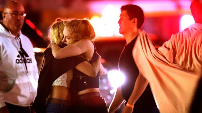 Patrons of the Borderline Bar and Grill comfort each other after a mass shooting at the thousand Oaks night spot in November.
