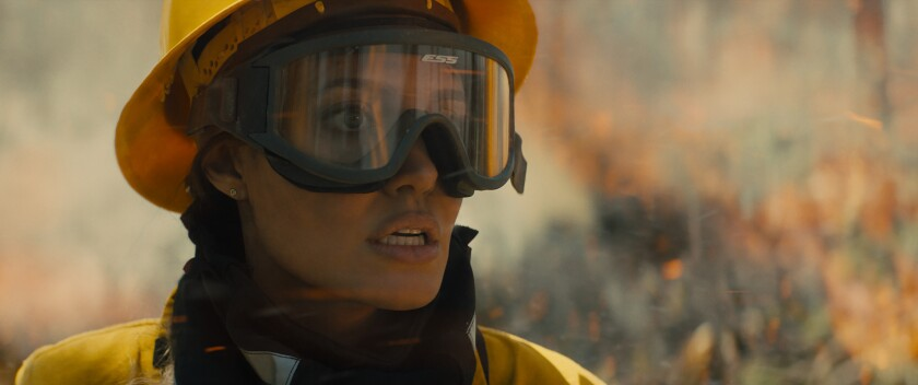 Playing a wildfire-fighter,  Angelina Jolie's character looks alarmed as flames burn in the background