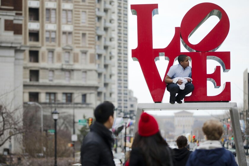 FILE - In this March 27, 2015, file photo, a young man climbs on a sculpture by Robert Indiana, at JFK Plaza, commonly known as Love Park, in Philadelphia. On Wednesday, Feb. 10, 2016, city officials broke ground on a $16.5 million, yearlong renovation of the park, requiring a temporary relocation of the park's Robert Indiana sculpture, expected to receive about four months of restoration work. (AP Photo/Matt Rourke, File)