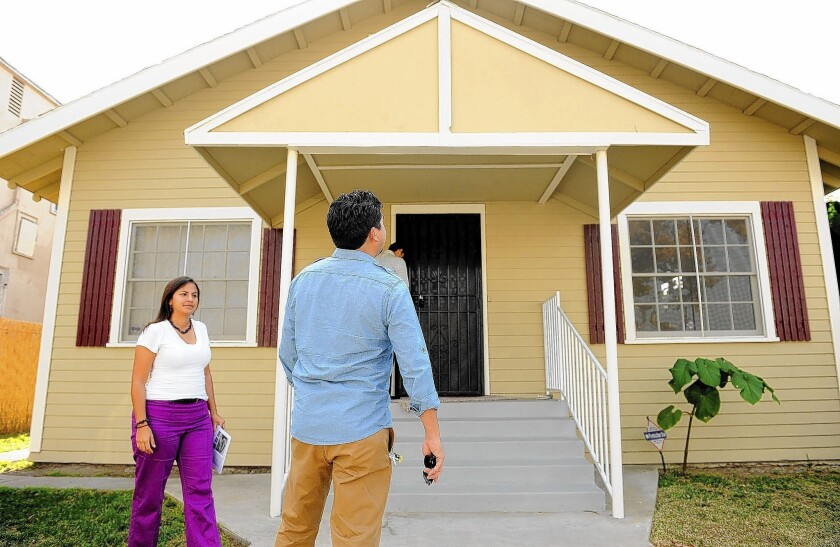 Citlali and Israel Gonzales inspect a house for sale in South Los Angeles. They wanted a home in a new development when they started their search a year ago, but found few choices.