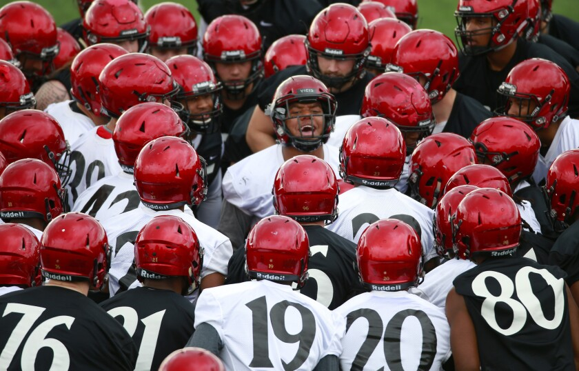 The San Diego State University football team gathers around linebacker Kyahva Tezino (center) before their first spring practice on March 4, 2019. (Photo by K.C. Alfred/San Diego Union-Tribune)