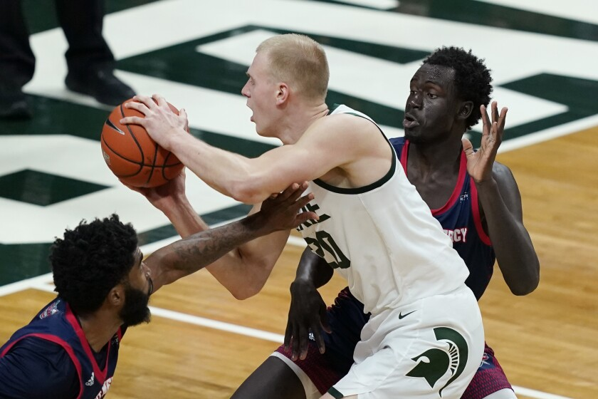 Michigan State forward Joey Hauser (20) is defended by Detroit Mercy guard Bul Kuol, during the second half of an NCAA college basketball game, Friday, Dec. 4, 2020, in East Lansing, Mich. (AP Photo/Carlos Osorio)