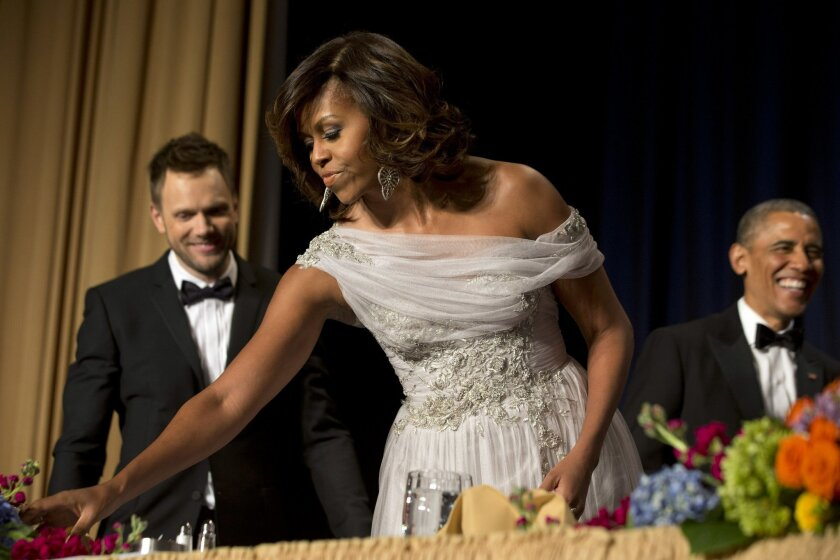 First lady Michelle Obama, center, takes her seat with Joel McHale, star of the NBC series Community, at left, and President Barack Obama, at right, during the centennial dinner of the White House Correspondents' Association (WHCA) at the Washington Hilton Hotel, Saturday, May 3, 2014, in Washington. (AP Photo/Jacquelyn Martin)