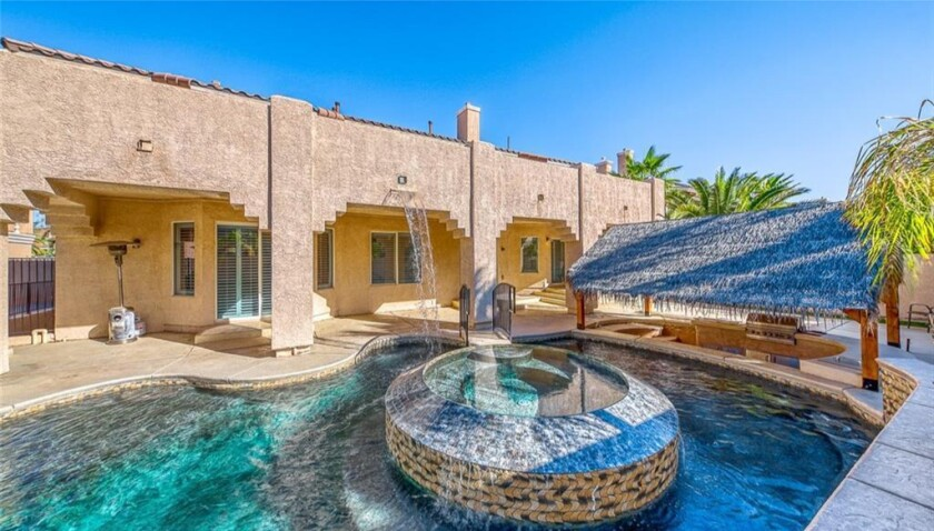 The two-story home opens to an entertainer's backyard with a cabana, pool, spa and swim-up bar.