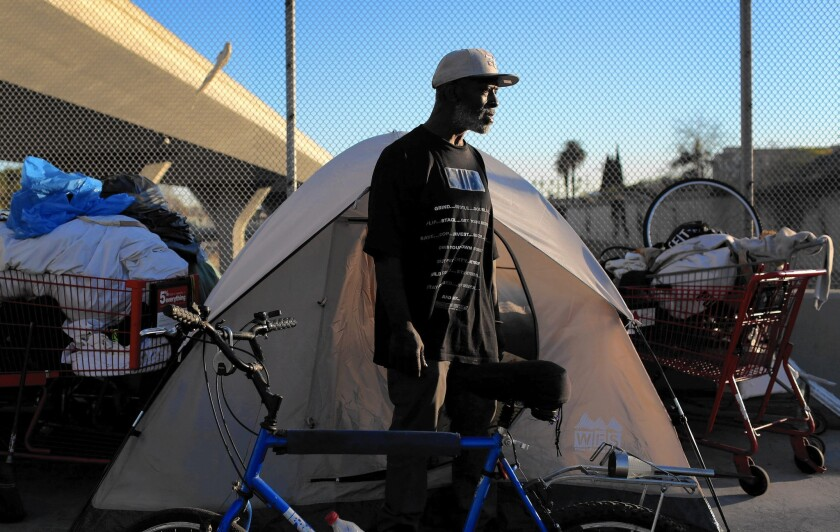 Willie Hadnot stands outside his tent on the 42nd Street overpass over the 110 Freeway. Activists last fall urged L.A. to declare a state of emergency as severe weather threatened the city's homeless population.