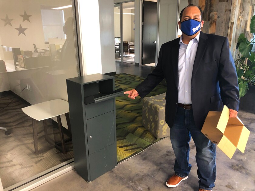 California Republican Party spokesman Hector Barajas demonstrates how to use one of the party's unofficial ballot drop boxes on Tuesday, Oct. 20, 2020, in Sacramento, Calif. The party had used this box to collect ballots at one if its field offices in Fresno, Calif. State Attorney General Xavier Becerra has asked a judge Tuesday to order the party to disclose the location of each drop box and provide contact information of every voter who used them. Becerra is investigating the party's use of the boxes. (AP Photo/Adam Beam)