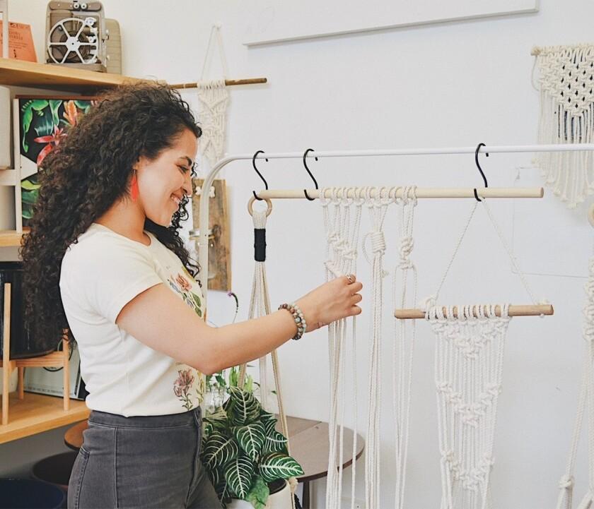 Lola Morales adjusts her white rope macramé plant hangers.