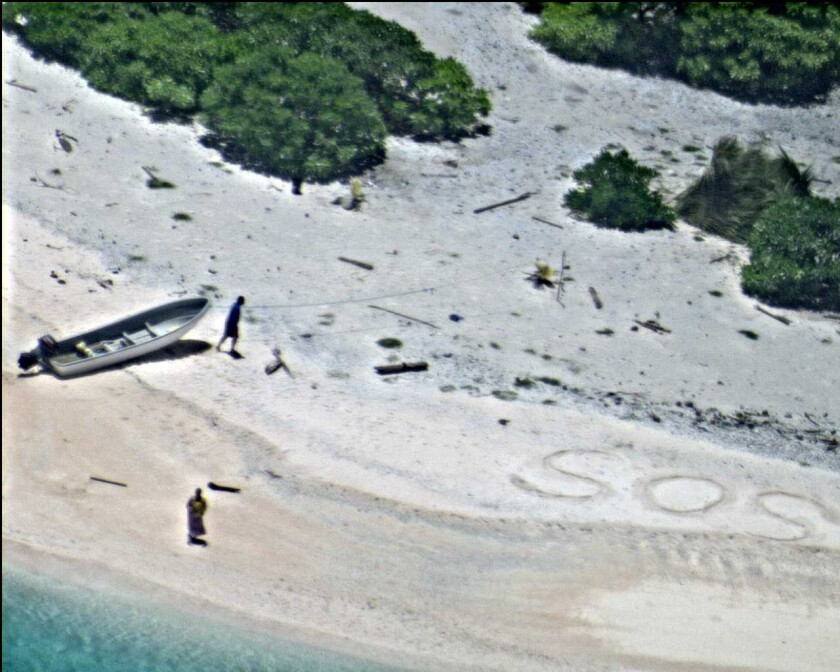 A pair of stranded mariners signal for help as a U.S. Navy P-8A Poseidon aircraft flies over in support of a Coast Guard search and rescue mission on an uninhabited island in Micronesia.