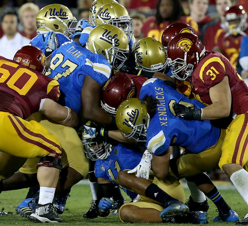 Trojans tailback Javorius Allen, center, is swarmed by the UCLA defense during the fourth quarter of a game on Nov. 30, 2013.
