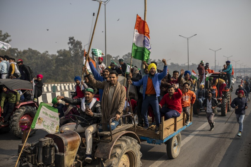 FILE - In this Jan. 26, 2021 file photo, protesting farmers ride tractors and shout slogans as they march to the capital breaking police barricades during India's Republic Day celebrations in New Delhi, India. Images of thousands of farmers streaming into India's capital to decry potentially devastating changes in agricultural policy can seem a world away, but the protests in New Delhi raise issues that resonate in the United States and have led to dramatic change in rural America. (AP Photo/Altaf Qadri, File)
