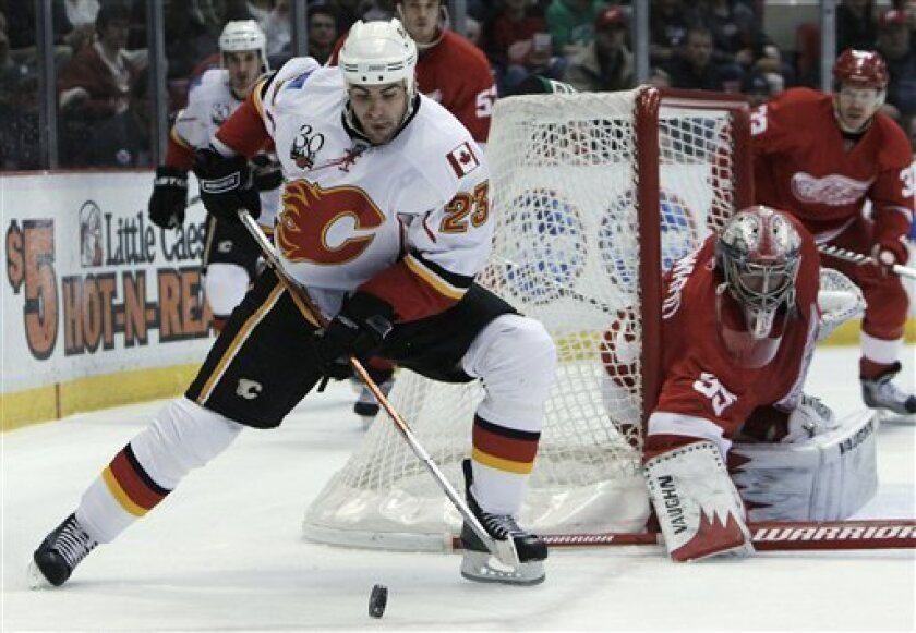 Calgary Flames' Eric Nystrom retrieves a rebound from a blocked shot by Detroit Red Wings goalie Jimmy Howard in the first period of an NHL hockey game in Detroit, Tuesday, March 9, 2010. (AP Photo/Paul Sancya)
