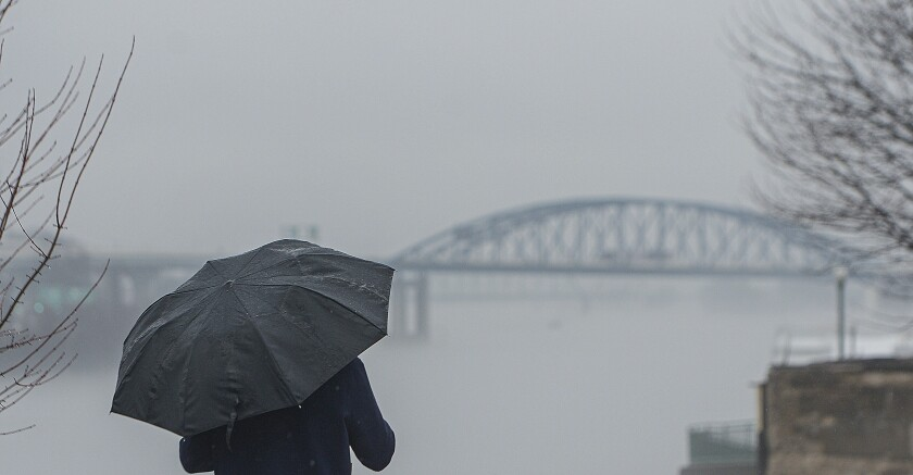 A man walks near the Kanawha River in Charleston, W.Va., on a foggy day