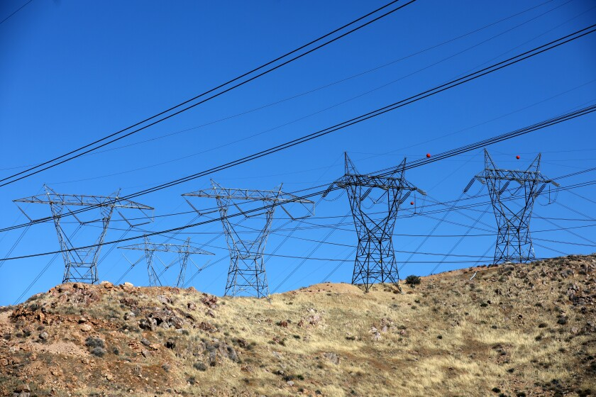 Electric transmission towers and lines on a dry hillside