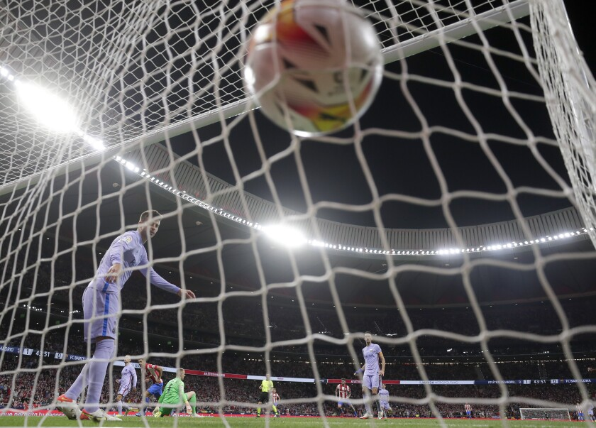 Barcelona's Gerard Pique looks round as Atletico Madrid's Luis Suarez, center rear, celebrates after scoring his side's second goal during the La Liga soccer match between Atletico Madrid and Barcelona at the Estadio Wanda Metropolitano in Madrid, Saturday, Oct. 2, 2021. (AP Photo/Manu Fernandez)
