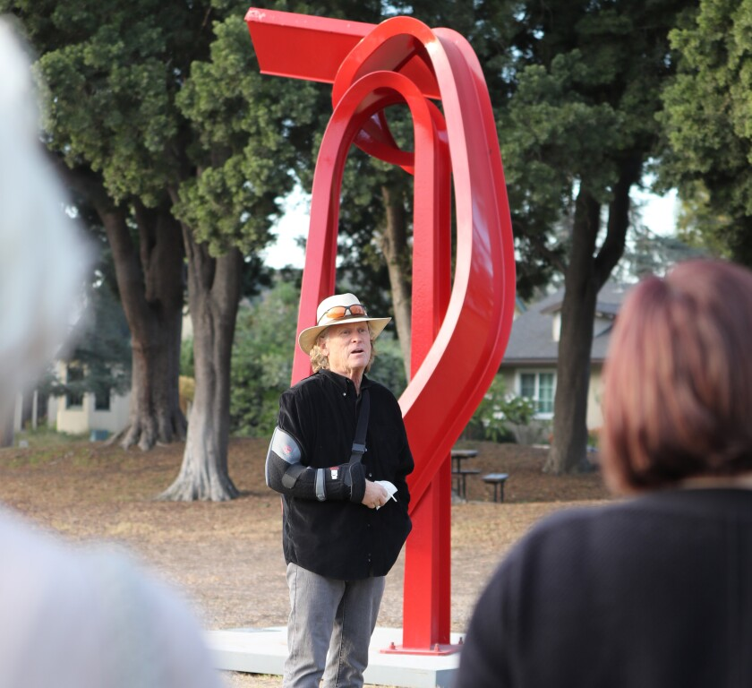 """Artist Bret Price stands next to his piece titled """"Godot"""" on Nov. 12."""