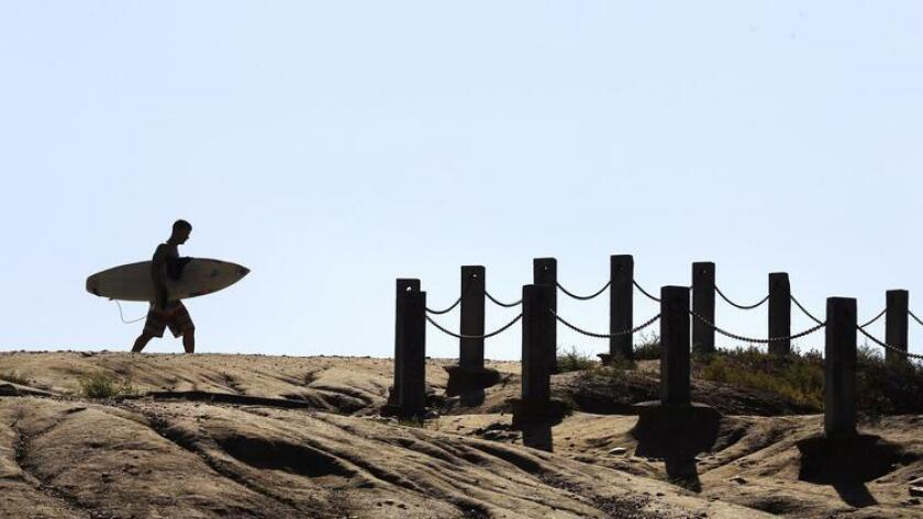 A Surfer heads to the walkway near the Torrey Pines Gliderport that leads to Black's Beach in La Jolla. (Howard Lipin)
