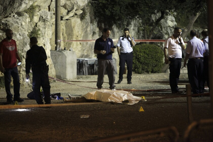 Israeli police work around the body of a Palestinian in Jerusalem on June 17. The man was one of three Palestinians who authorities said attacked Israeli officers near Jerusalem's Old City.