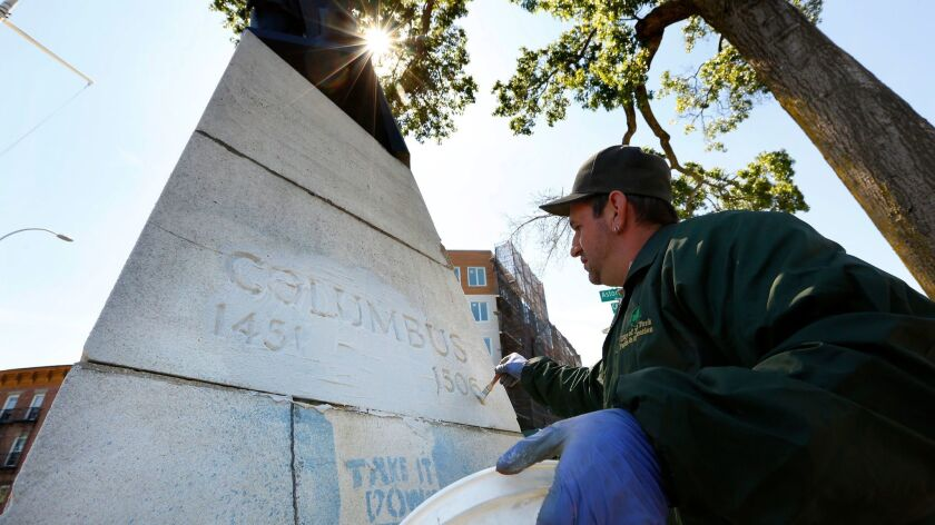 """A statue of Christopher Columbus was marked with graffiti in Columbus Triangle park in Queens, N.Y., overnight. An employee of the New York Parks Department works to remove the writing, which said, """"Tear it down. Don't Honor Genocide."""""""