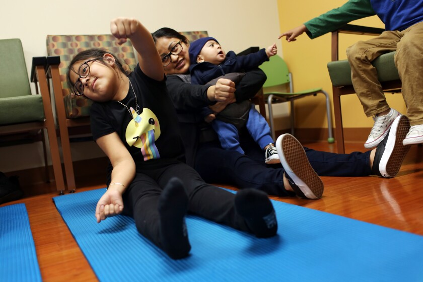 Irie Mazas, 7, with her mother, Miriam Bautista, center, and brother, Carlos Mazas, during a BodyWorks class at Children's Hospital Los Angeles.