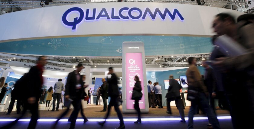 People walk past Qualcomm's stand during the Mobile World Congress in Barcelona, Spain in this February 24, 2016, file photo. Last week, the San Diego technology giant said it paid $19.5 million to settle claims it didn't offer equal pay and promotion opportunities to its women employees.