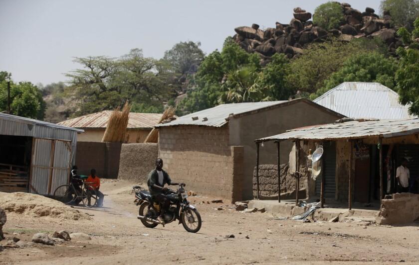 ARCHIVO - En esta fotografía de archivo un hombre no identificado maneja su motocicleta frente a casas en Chibok, Nigeria. Los atacantes con explosivos en un pueblo en el noroeste de Nigeria en donde el Boko Haram secuestró a cientos de colegialas, eran hombres con hiyabs y explosivos colocados en sus espaldas de tal forma que parecieran bebés, dijo el ejército del país. (Foto AP/Sunday Alamba, Archivo)