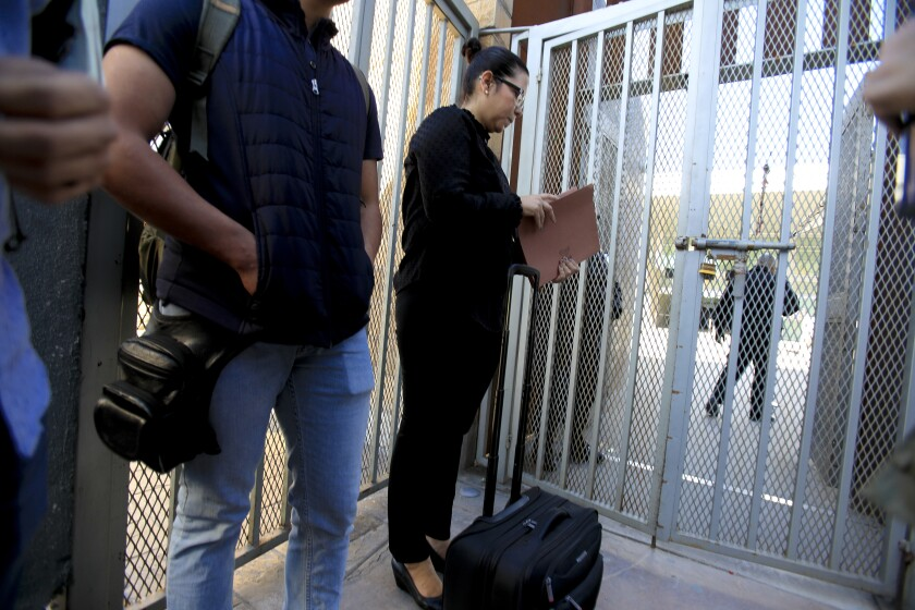 On Tuesday, December 10, 2019 standing on the Mexico side of the border at the PedWest U.S. port of entry in San Ysidro, Margaret Cargioli (r), managing attorney for Immigrant Defenders Law Center in San Diego waits with Jose, 20 (left) to speak with a CBP supervisor. Cargioli and Jose were allowed to cross into the U.S. According to Cargioli, she an her Jose earlier tried to cross legally at the San Ysidro port of entry on December 6th with all the necessary paperwork including the required 9k immigration bond, but was denied entry.