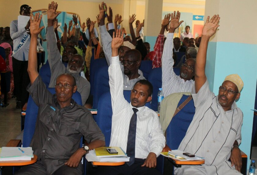 Somali MPs raise their hands during session to impeach the Somali Prime Minister Abdi Farah Shirdon, in Mogadishu, Somalia, Monday, Dec. 2, 2013. Lawmakers in Somalia voted Monday to oust the country's prime minister and his Cabinet after 14 months in office. Lawmakers voted 184-65 to oust Prime Minister Abdi Farah Shirdon and his 10-member Cabinet, Parliament Speaker Sheik Osman Jawari said. Shirdon will remain in office until President Hassan Sheikh Mohamud nominates a new prime minister, who will then have 30 days to appoint a new Cabinet, Jawari said. (AP Photo/Farah Abdi Warsameh)