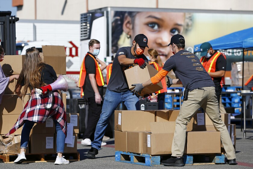 Employees unload boxes of frozen food on Thursday at Second Harvest's distribution facility in Irvine.