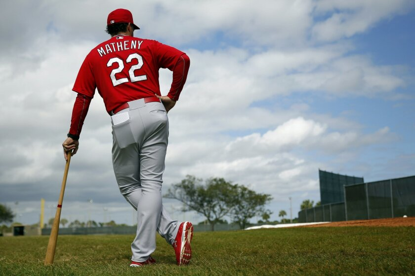 St. Louis Cardinals manager Mike Matheny leans on a bat as he prepares to watch pitchers throw during spring training baseball practice Sunday, Feb. 21, 2016, in Jupiter, Fla. (AP Photo/Jeff Roberson)