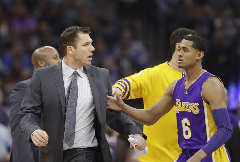 Lakers guard Jordan Clarkson (6) tries to guide Coach Luke Walton, left, to the locker room after he was ejected during the first quarter on Monday.
