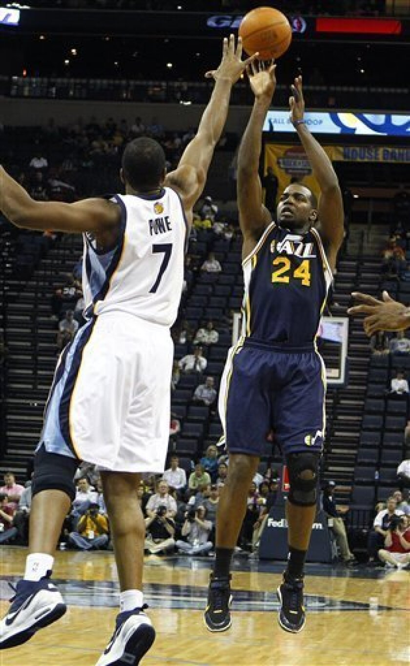 Utah Jazz's Paul Millsap, right, puts up a shot over Memphis Grizzlies' Loen Powe, left, during the second half of an NBA basketball game in Memphis, Tenn., Monday, March 21, 2011. (AP Photo/Mark Weber)