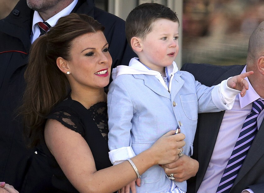 FILE - In this Saturday April 6, 2013 file photo, Coleen Rooney, left, wife of soccer player Wayne, and her son Kai, right, at Aintree Racecourse, Liverpool, England. The wives of two of English soccer's most high-profile players have on Wednesday, Oct. 9, 2019 become embroiled in a spat on Twitter about the leaking of information to a tabloid newspaper. Wayne Rooney's wife accused Jamie Vardy's wife of informing The Sun about details of her private Instagram stories. (AP Photo/Scott Heppell, file)