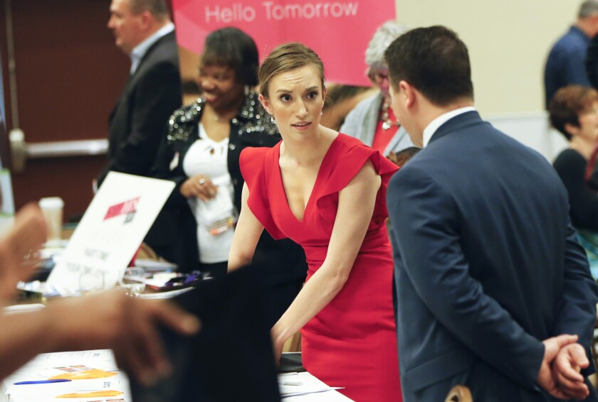 Recruiters work their booths at a job fair in Pittsburgh on March 30.