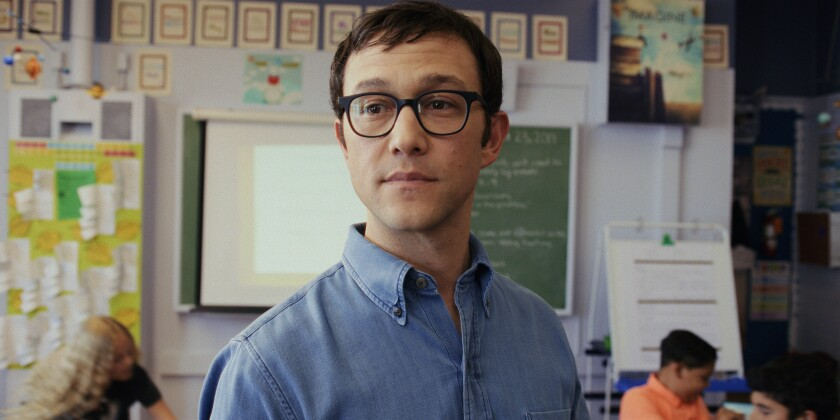 A teacher wearing glasses and a denim shirt in his fifth-grade classroom