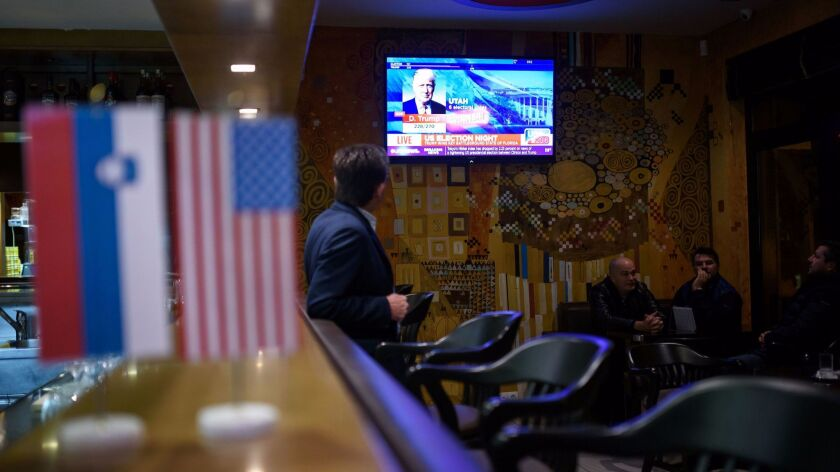 Residents of Sevnica, Slovenia, watch as U.S. presidential election results are shown on television on Nov. 9.