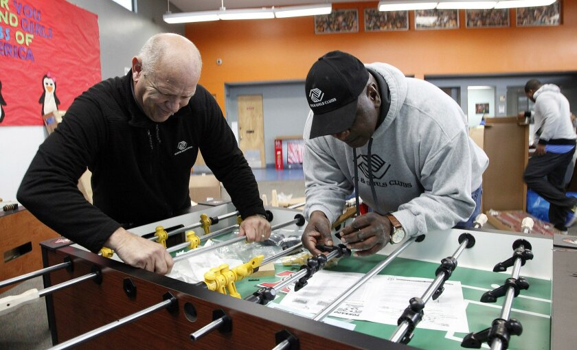 Eric Osborne (left) and John Miller of the Vista Boys & Girls Club assemble a table soccer game in the club's revamped game room on Monday.