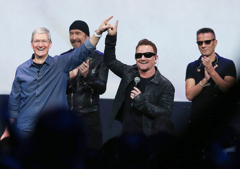 Apple CEO Tim Cook, left, greets the crowd with U2 singer Bono, second from right, as The Edge, second from left, and Larry Mullen Jr. look on during an Apple special event in Cupertino, Calif.